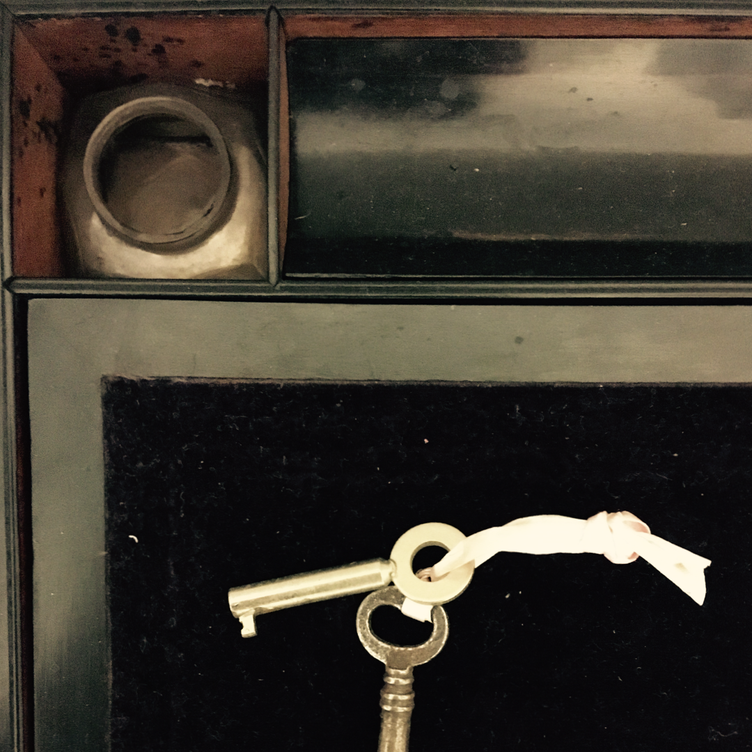 An inkwell and small set of keys in the interior of an antique writing slope.