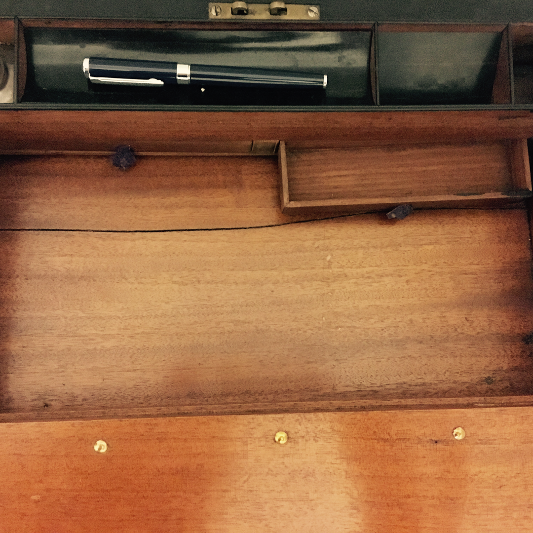 The interior of an antique writing slope, with one small secret drawer pulled open.