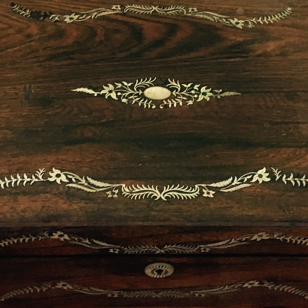 The top of an antique writing box, in dark wood with a delicate foliage border in opalescent shell inlay.