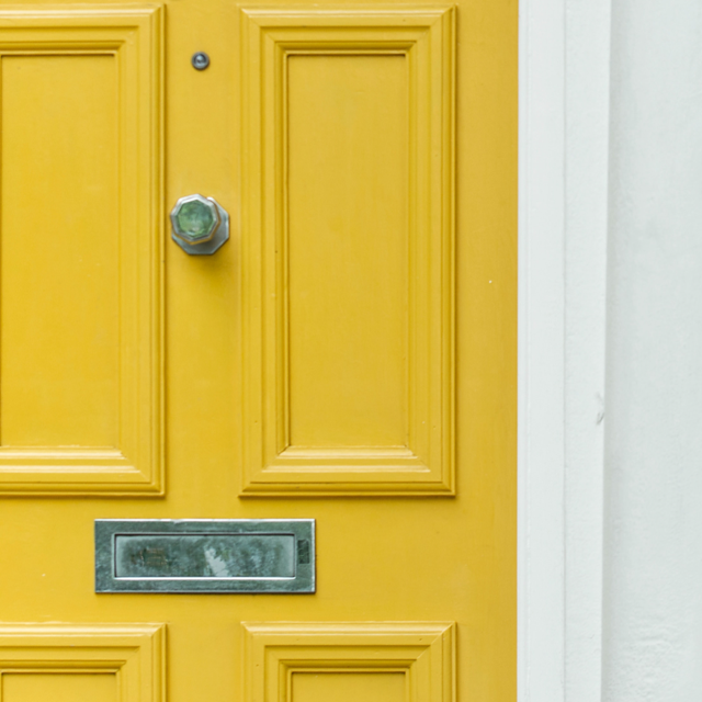 Close-up of a yellow front door.